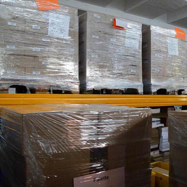 Fulfillment: Lager, Paletten mit Broschüren, in Kartons verpackt, eingeschweißt